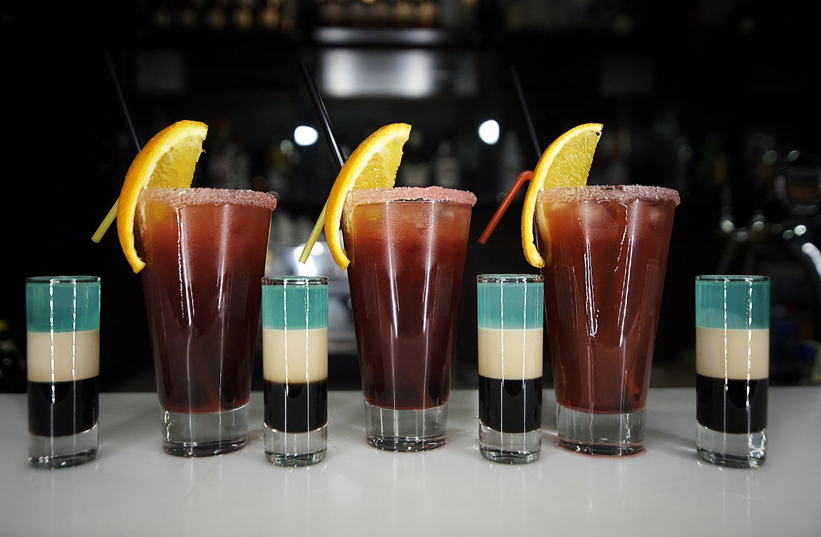 Multicolored shots and cocktails on a bar counter against a dark background