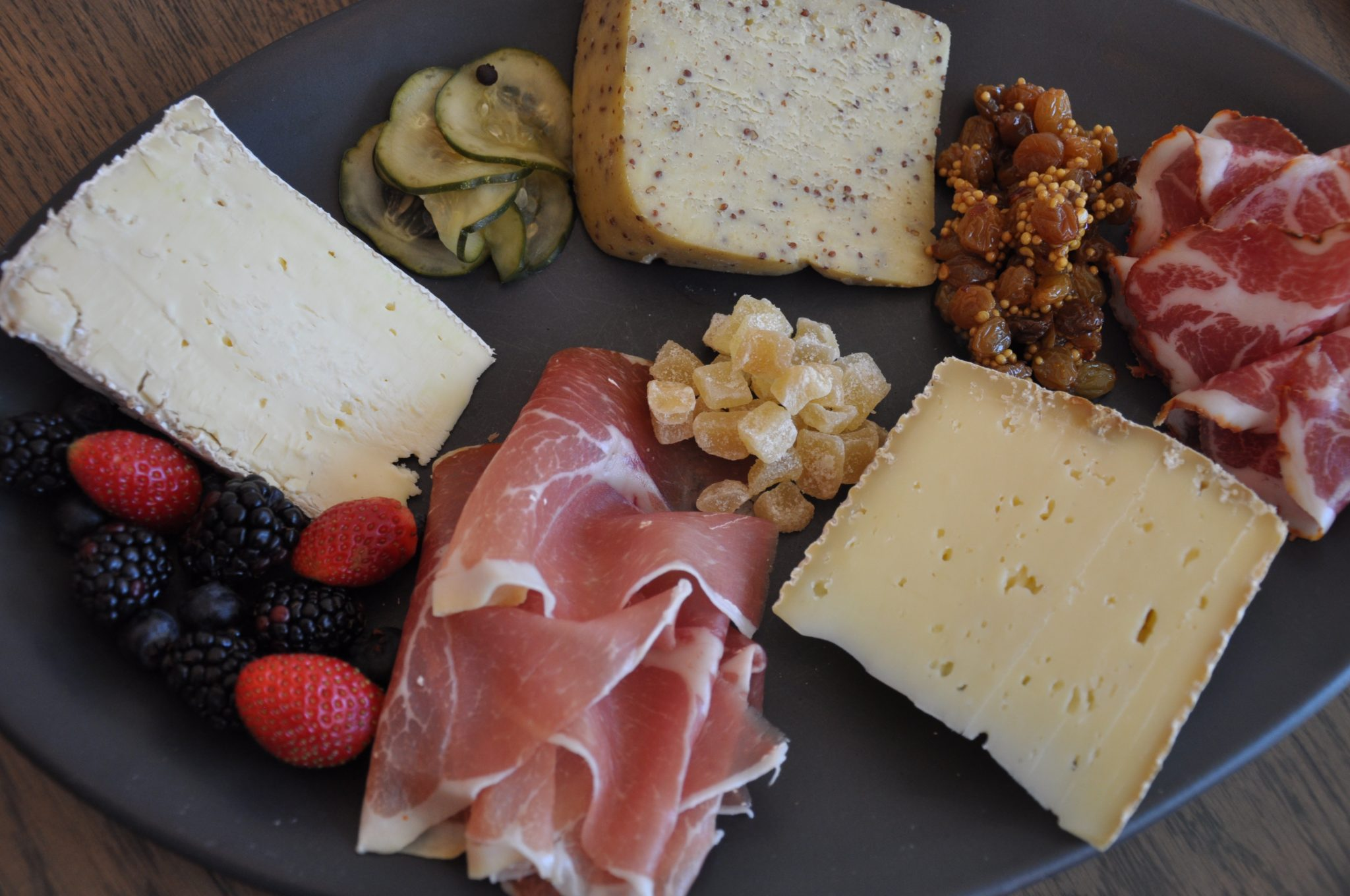 Charcuterie board with cheese, fruit, meat, pickles, raisins and dried fruit