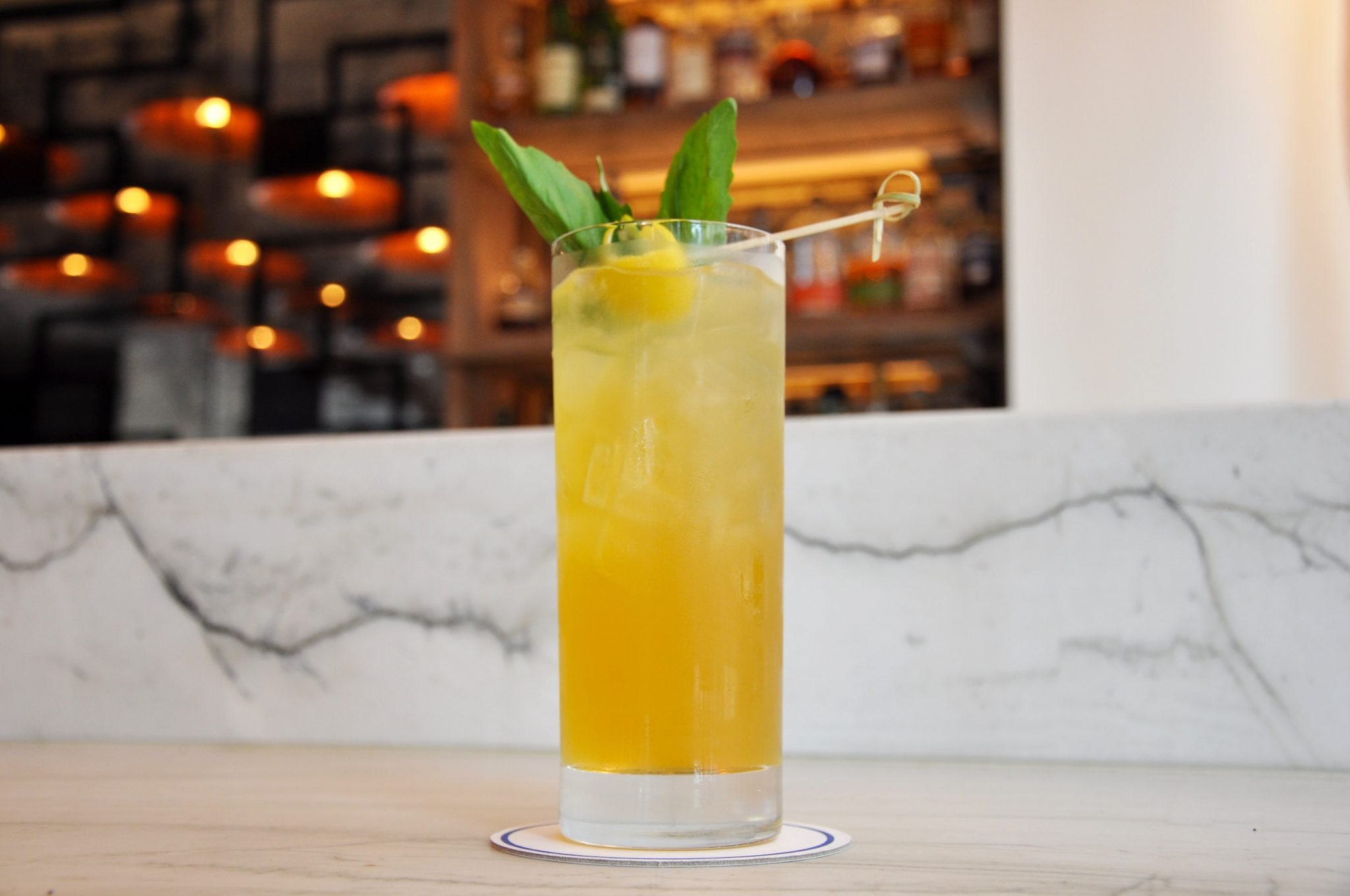 Yellow cocktail with mint and lemon peel on a marble counter top