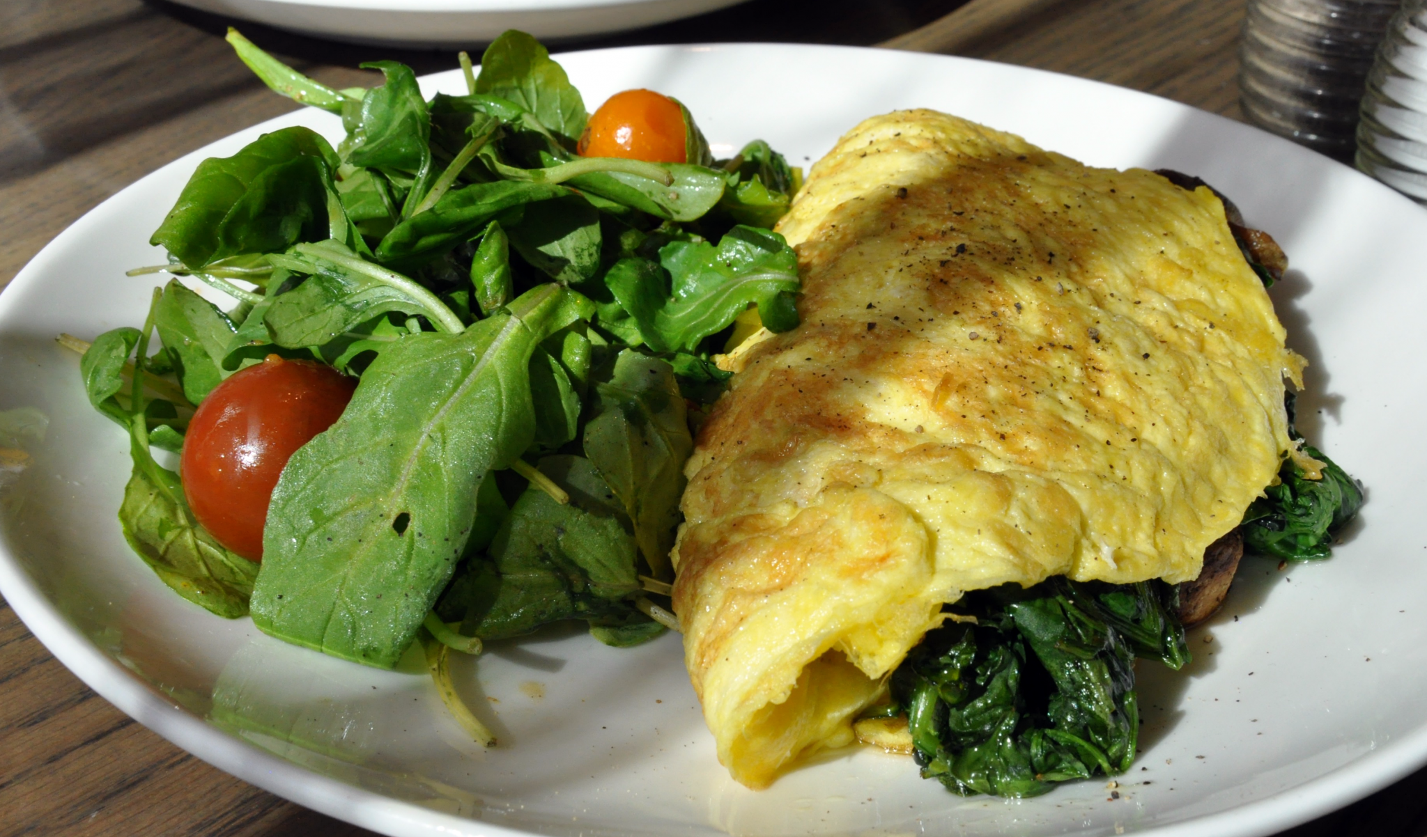 Breakfast egg omelet with spinach and mushrooms served with arugula and tomato salad